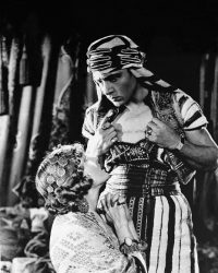 """(Original Caption) Rudolph Valentino and Vilma Banky are shown in """"Son of the Shiek,"""" 1926. Banks is shown kneeling infront of Valentino."""