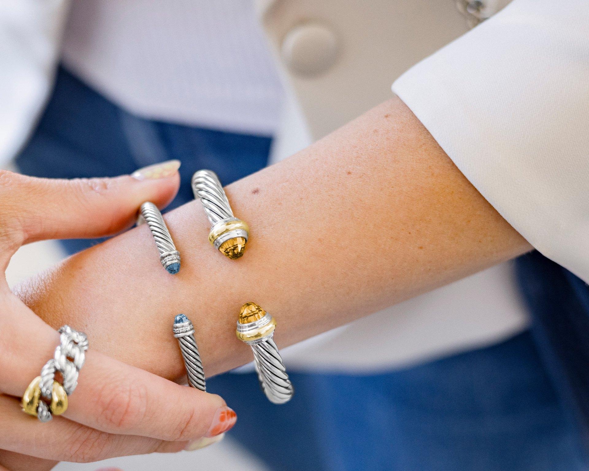 Two David Yurman cable bracelets on model's wrist and David Yurman ring lifestyle image