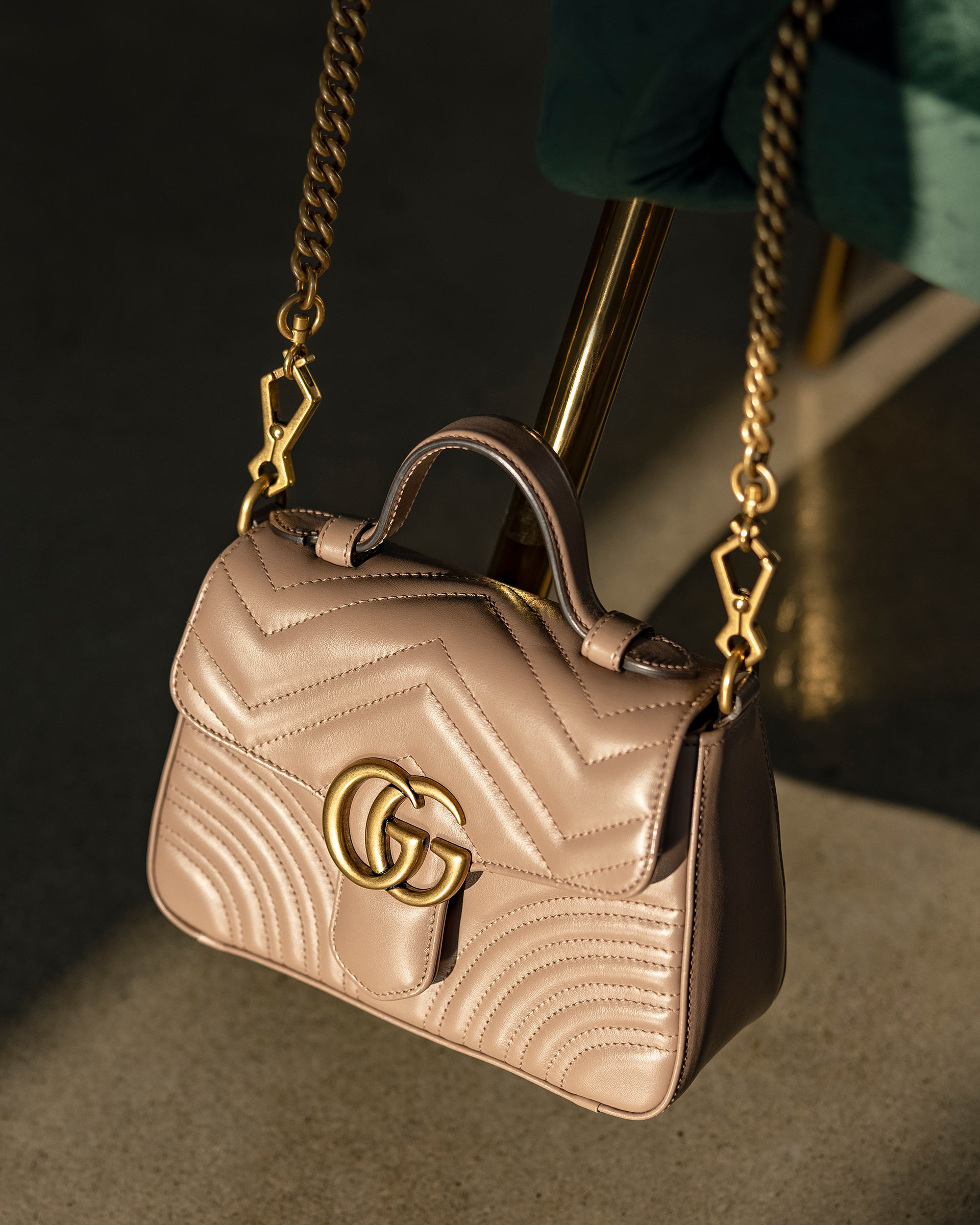 Lifestyle image of Authentic Gucci Marmont Top Handle Bag in beige at FASHIONPHILE