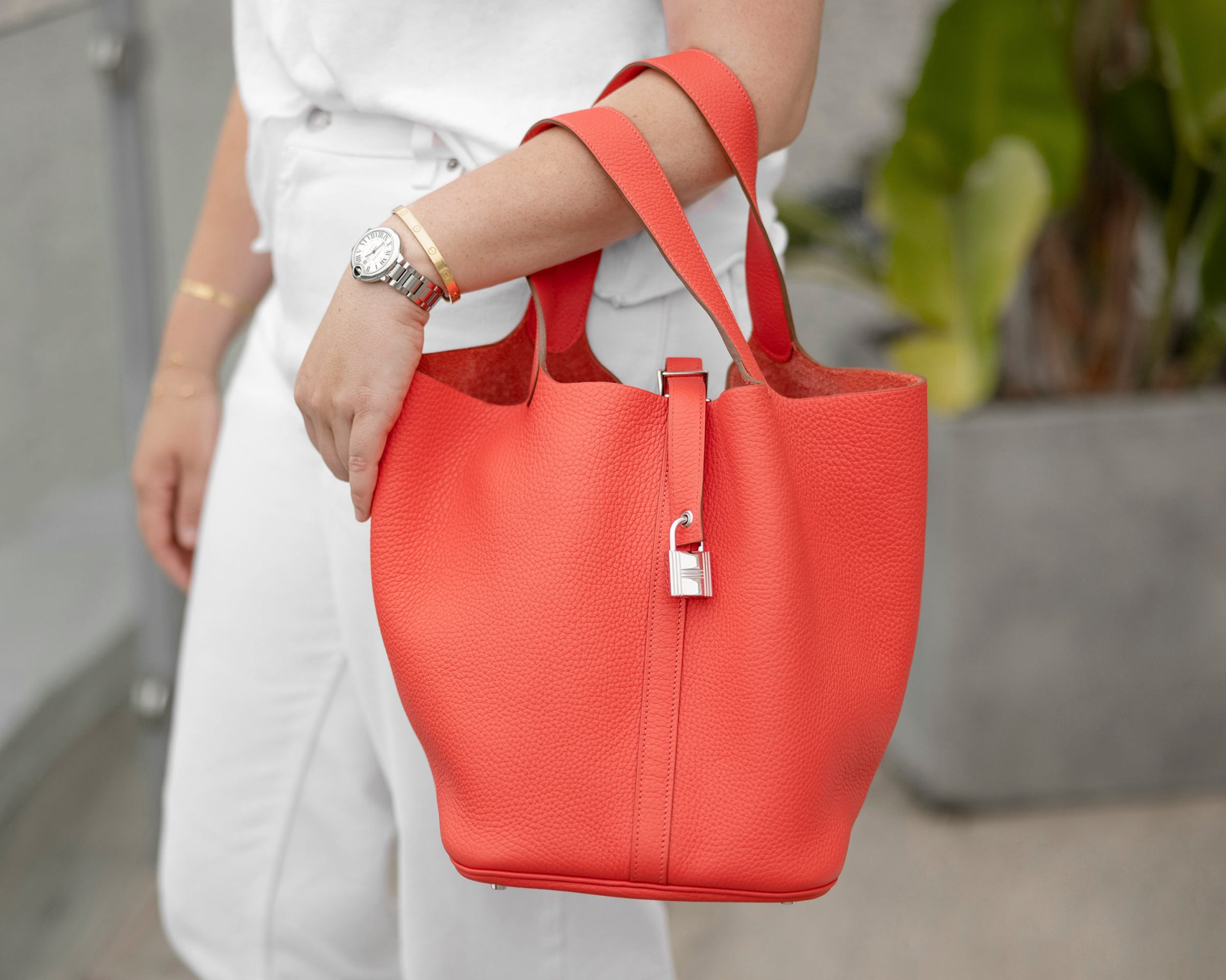 lifestyle photo of coral pink Hermes Picotin on model wearing white and designer jewelry