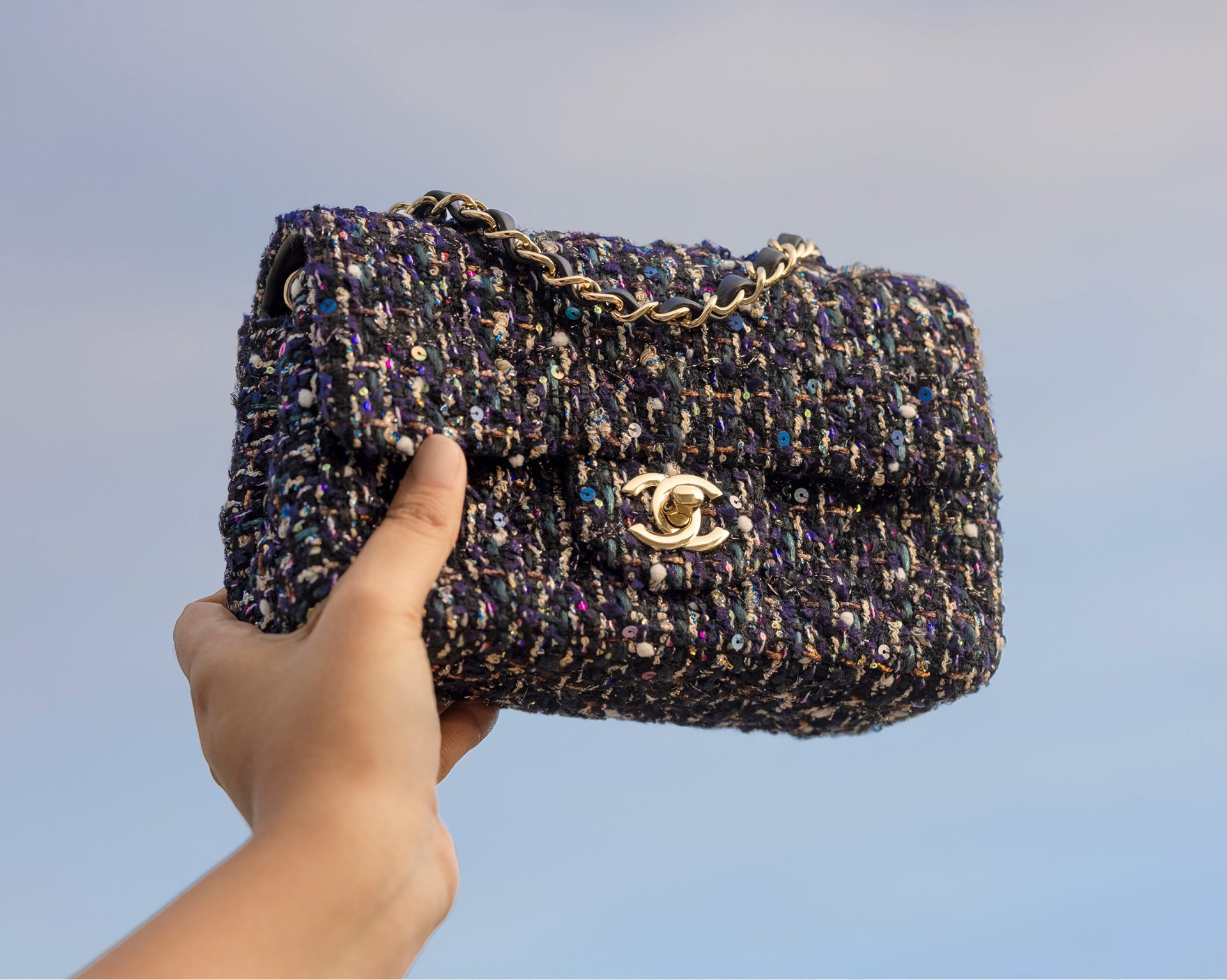lifestyle image of Chanel tweed flap bag being held up in the air